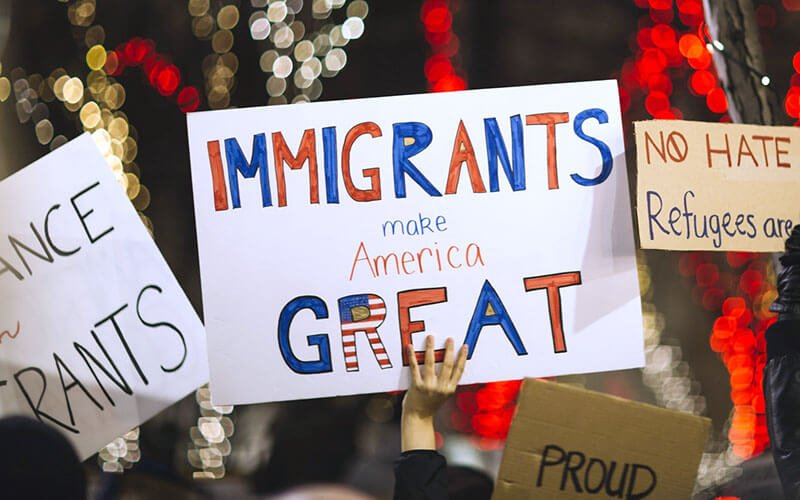 woman holding a sign immigrants make america great