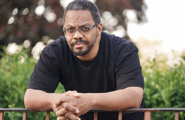 Black man with glasses with a black shirt